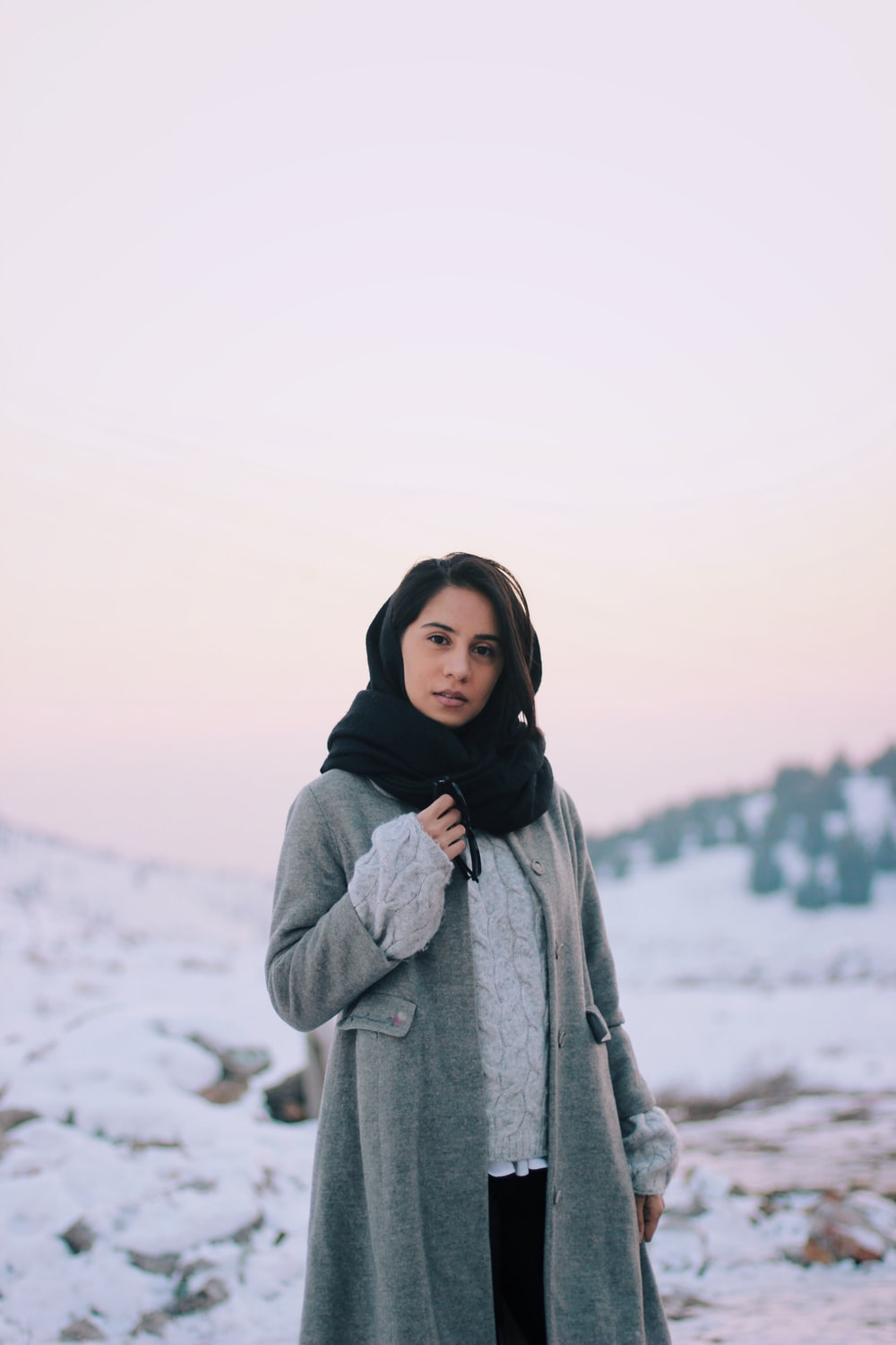 woman in gray coat standing on snow covered ground during daytime
