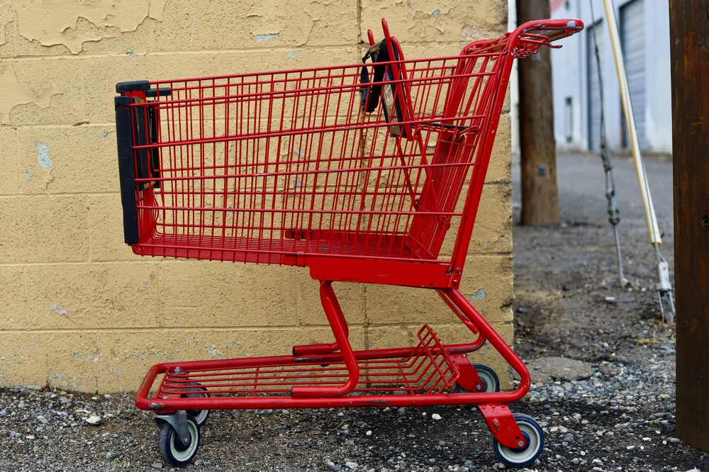 red shopping cart on gray concrete floor