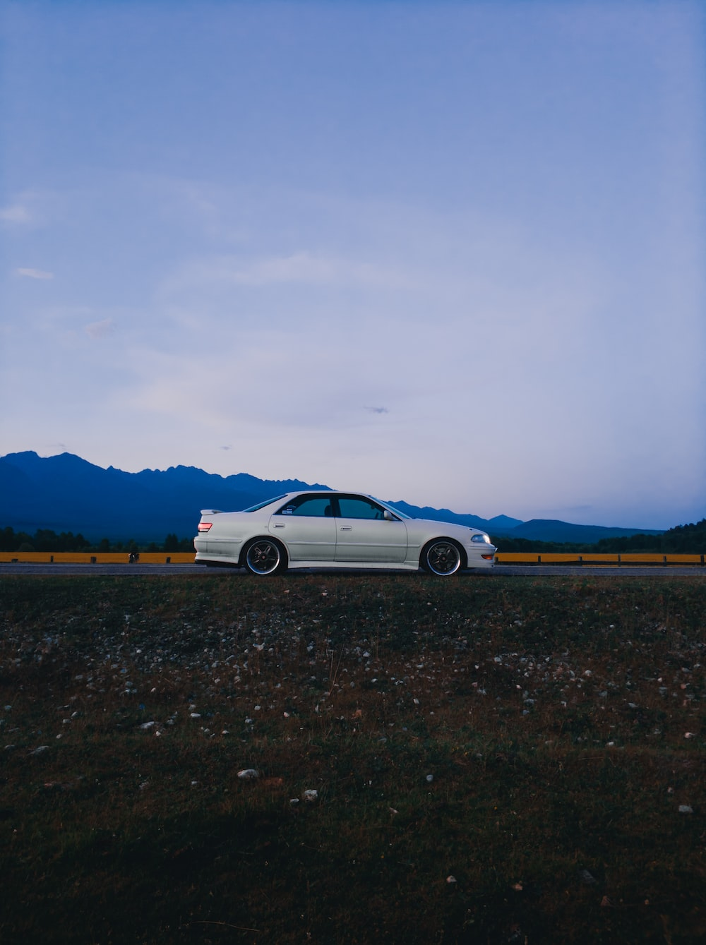 white coupe on brown dirt road during daytime