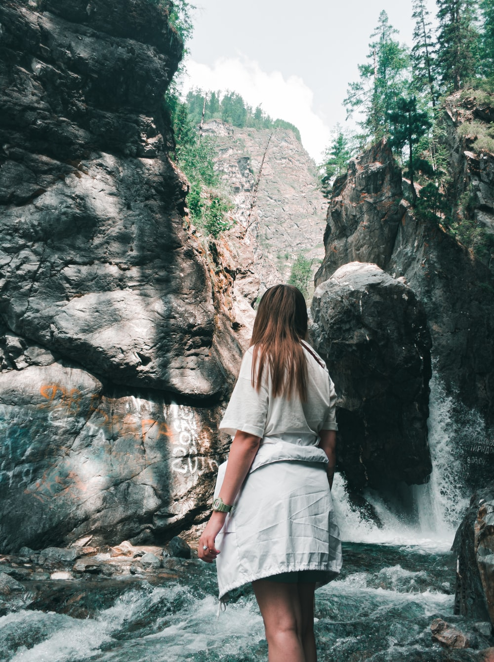 woman in white shirt and white skirt standing near waterfalls during daytime
