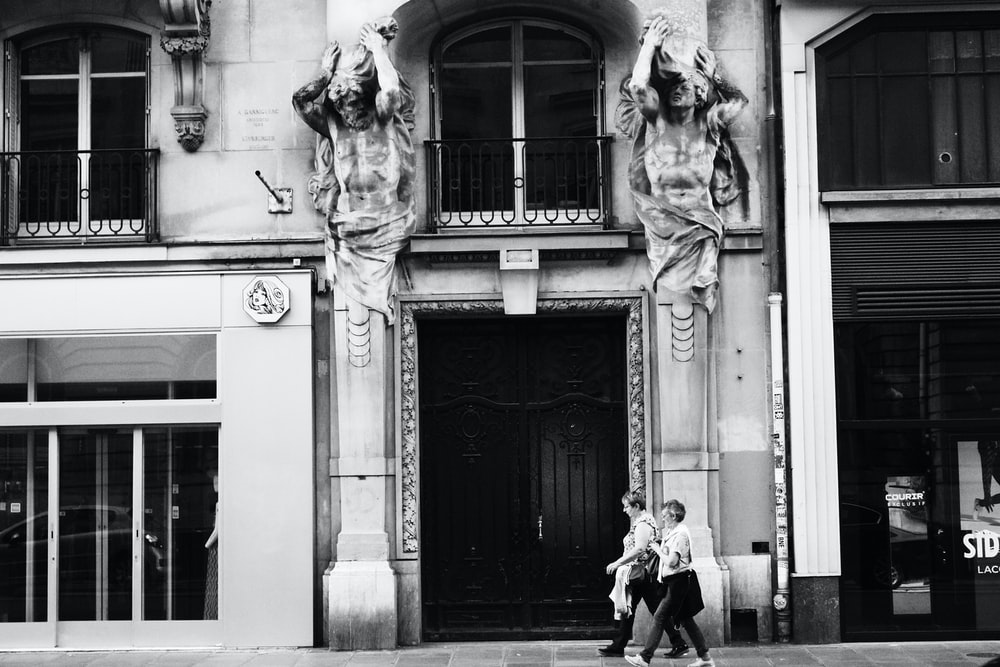 grayscale photo of man and woman standing in front of building