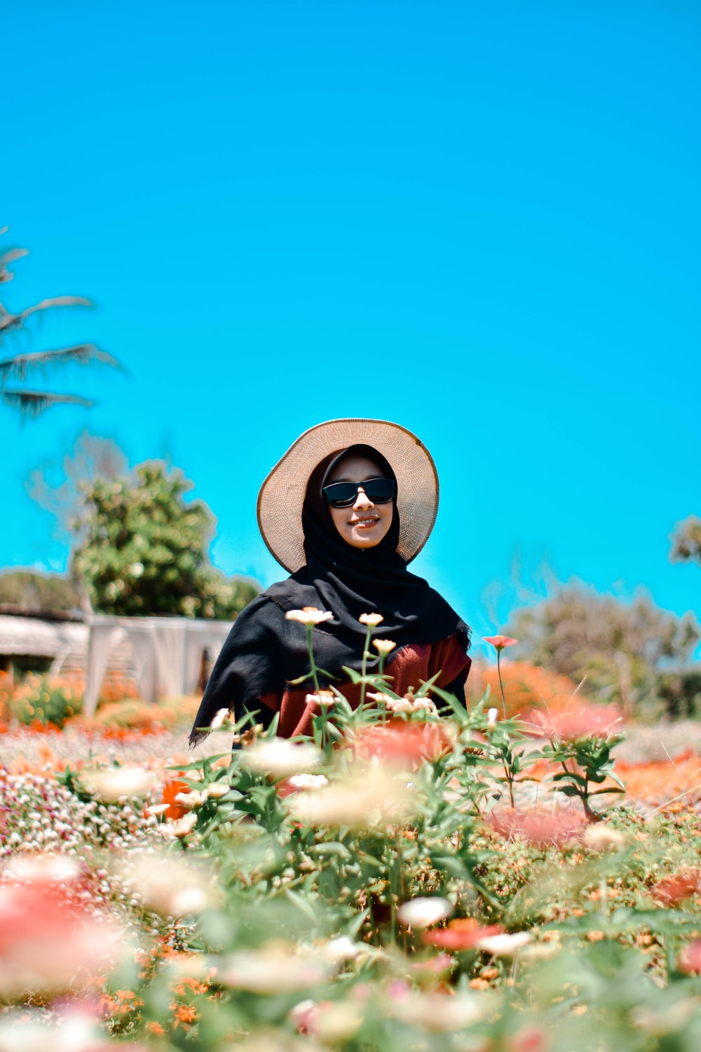woman in black and white hijab sitting on brown dried leaves during daytime