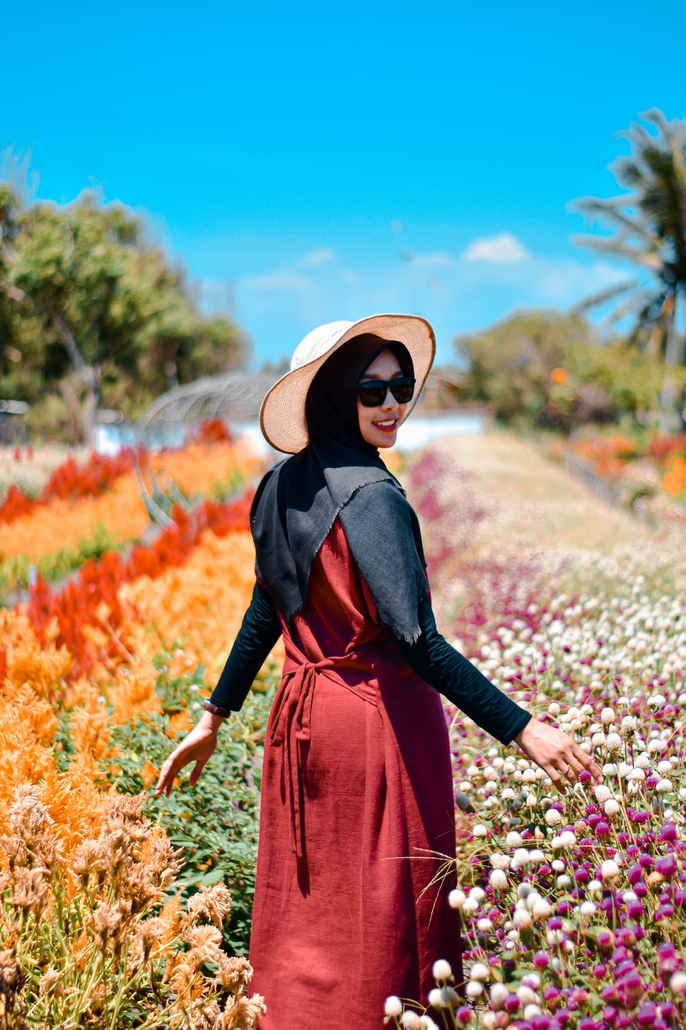 woman in black leather jacket and brown sun hat standing on flower field during daytime