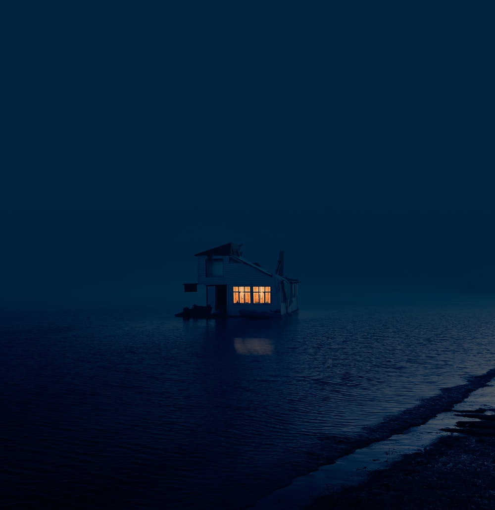 brown wooden house on sea shore during night time