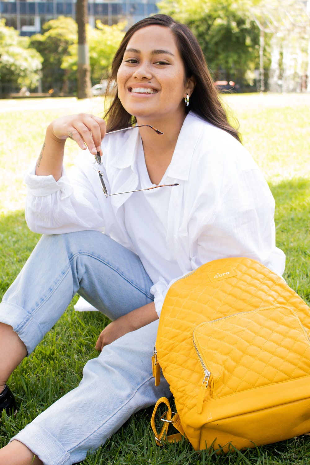 woman in white dress shirt and blue denim jeans sitting on green grass field during daytime