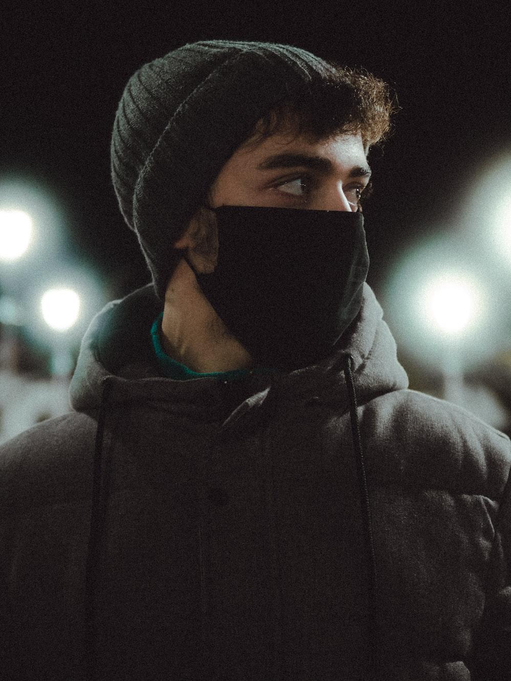 man in black hoodie wearing black knit cap