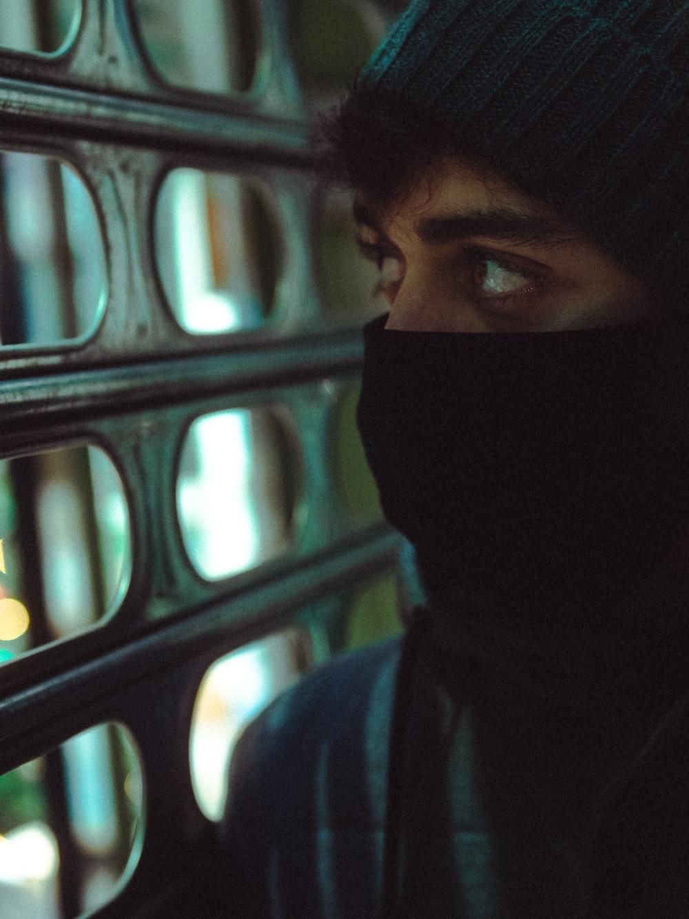 person in black hijab near black metal fence