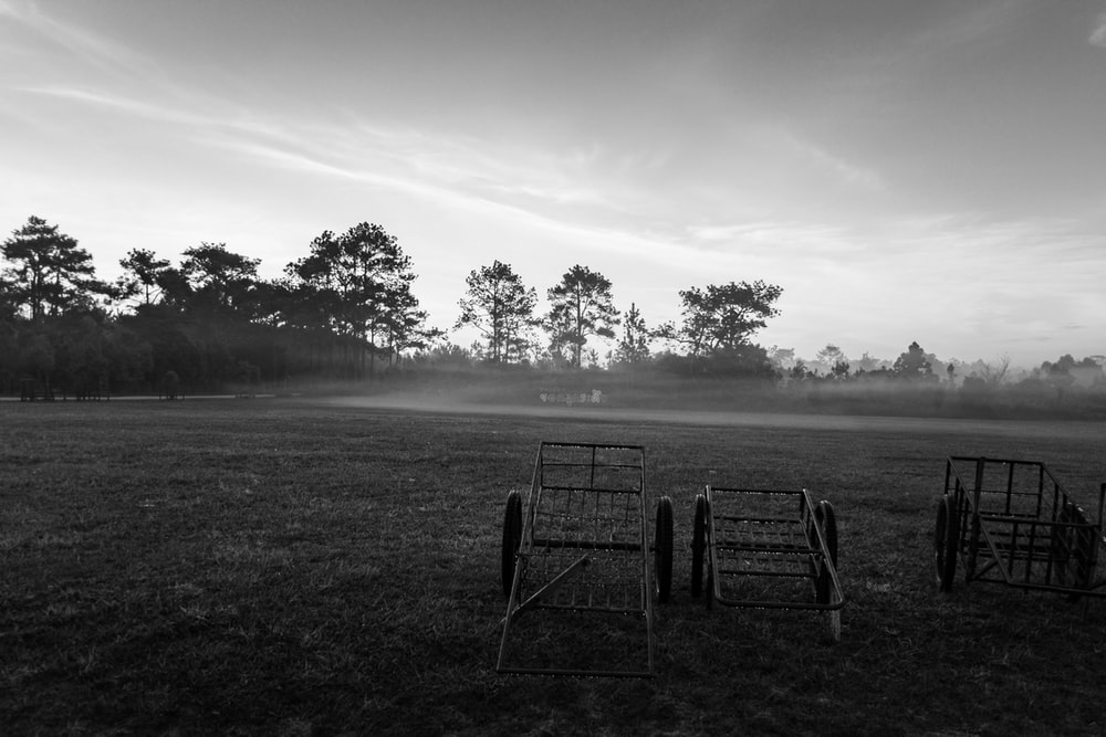 grayscale photo of a metal chair on a field