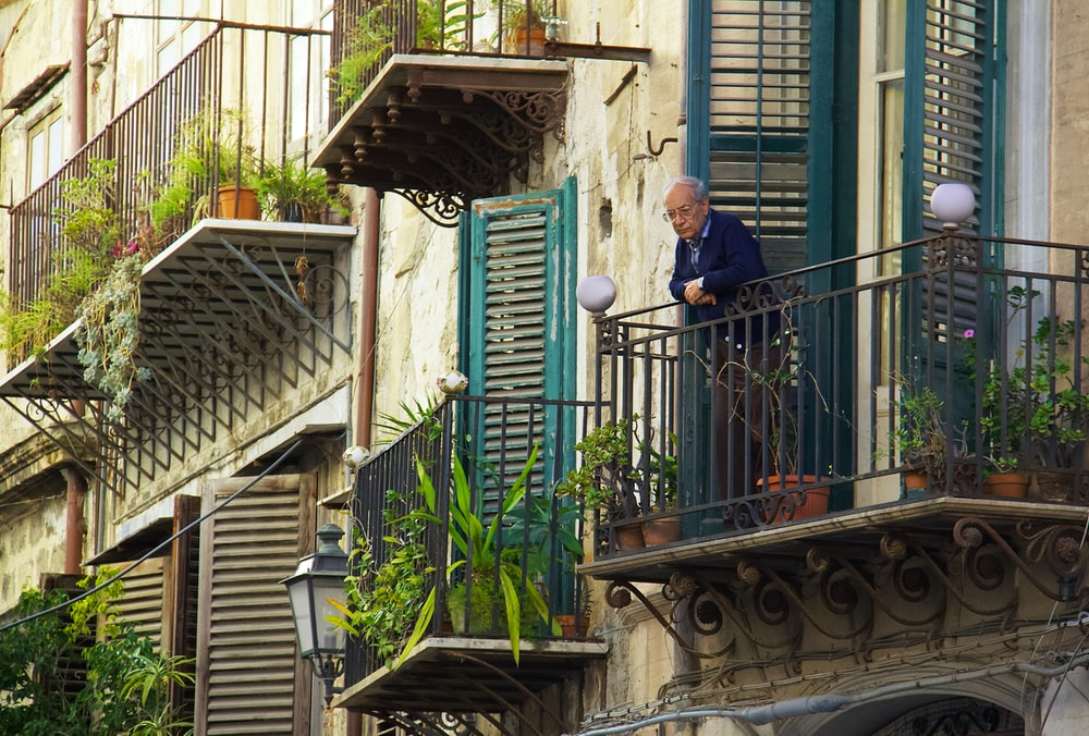 man in blue jacket standing on the balcony