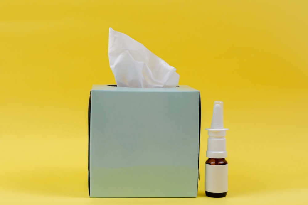 white and brown bottle beside white tissue box