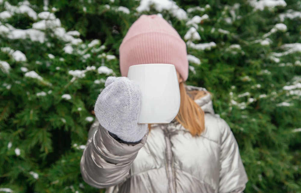 woman in gray jacket and red knit cap covering face with white paper