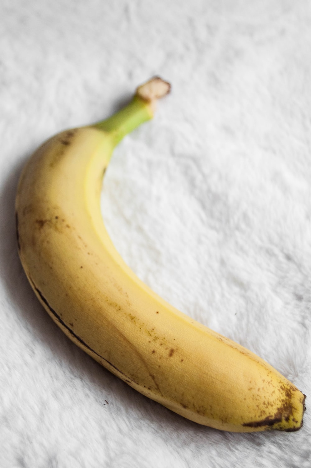 yellow banana on white textile