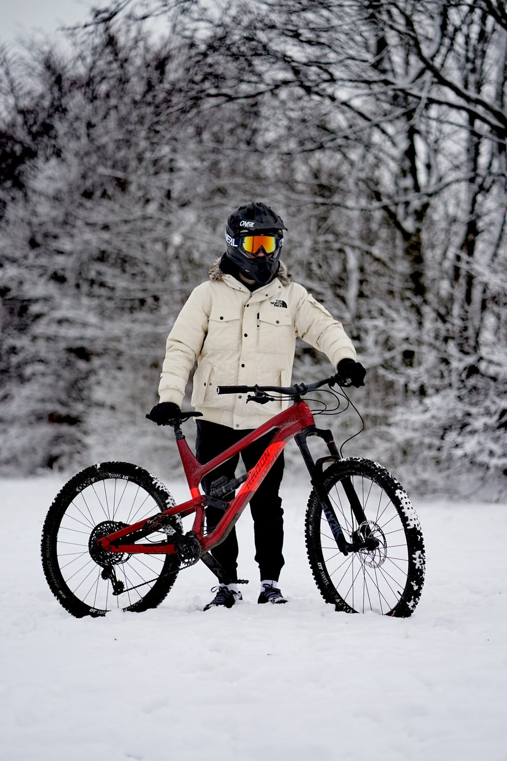 person in brown jacket riding red mountain bike on snow covered ground during daytime