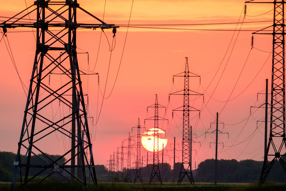 silhouette of electric post during sunset