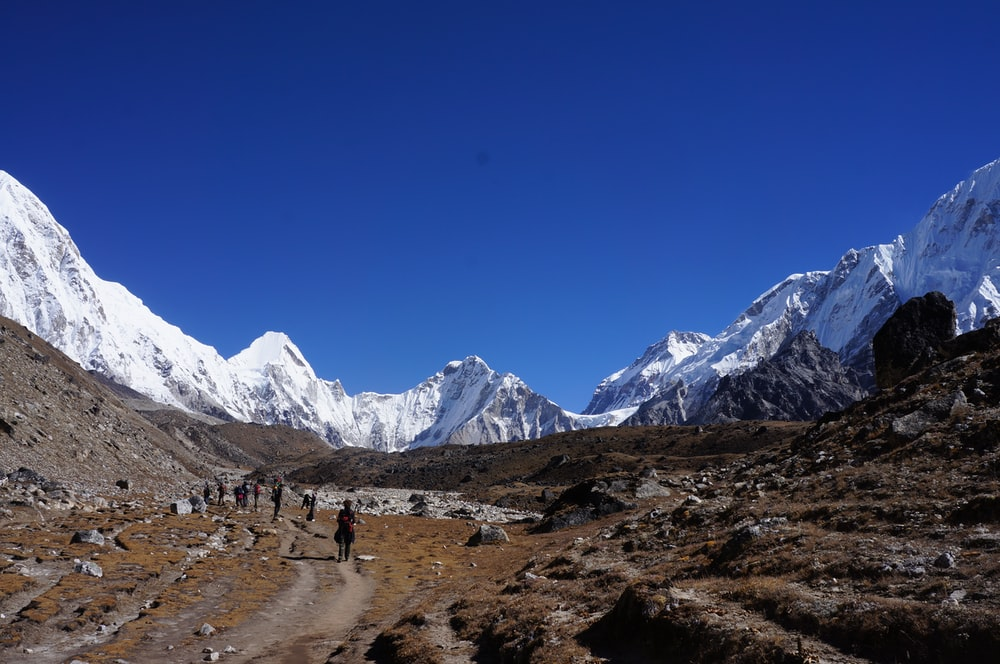 people walking on dirt road near snow covered mountains during daytime