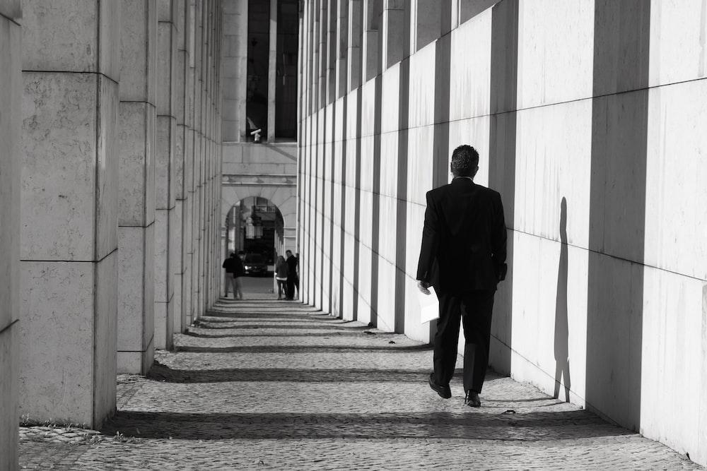 man in black suit walking on hallway