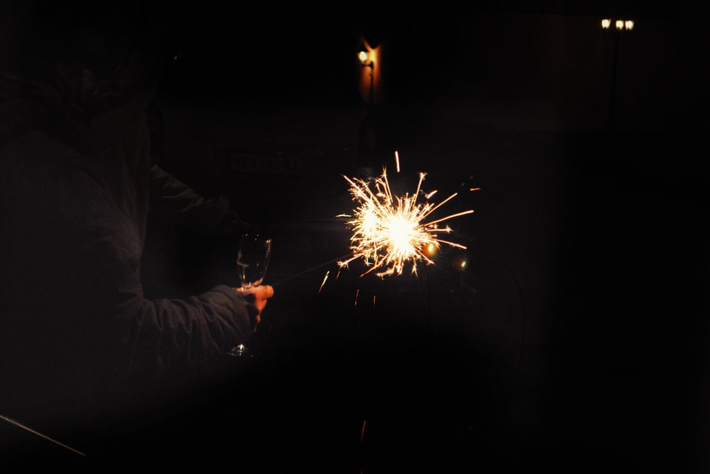 person holding sparkler during nighttime