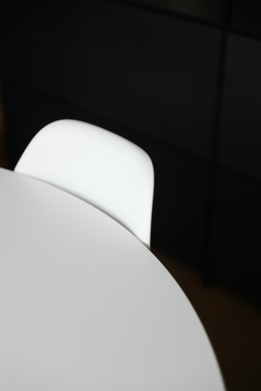 white plastic chair beside white table