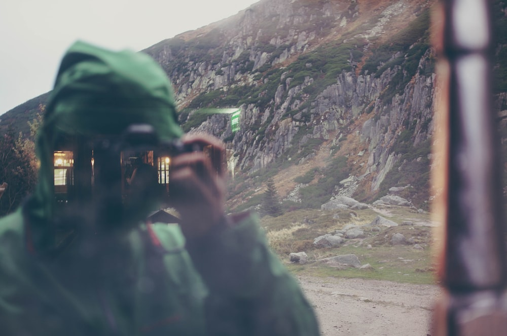 person in green jacket taking photo of mountain during daytime