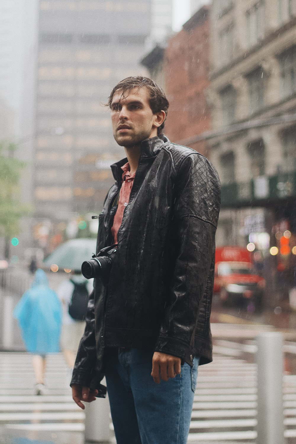 man in black leather jacket standing on street during daytime