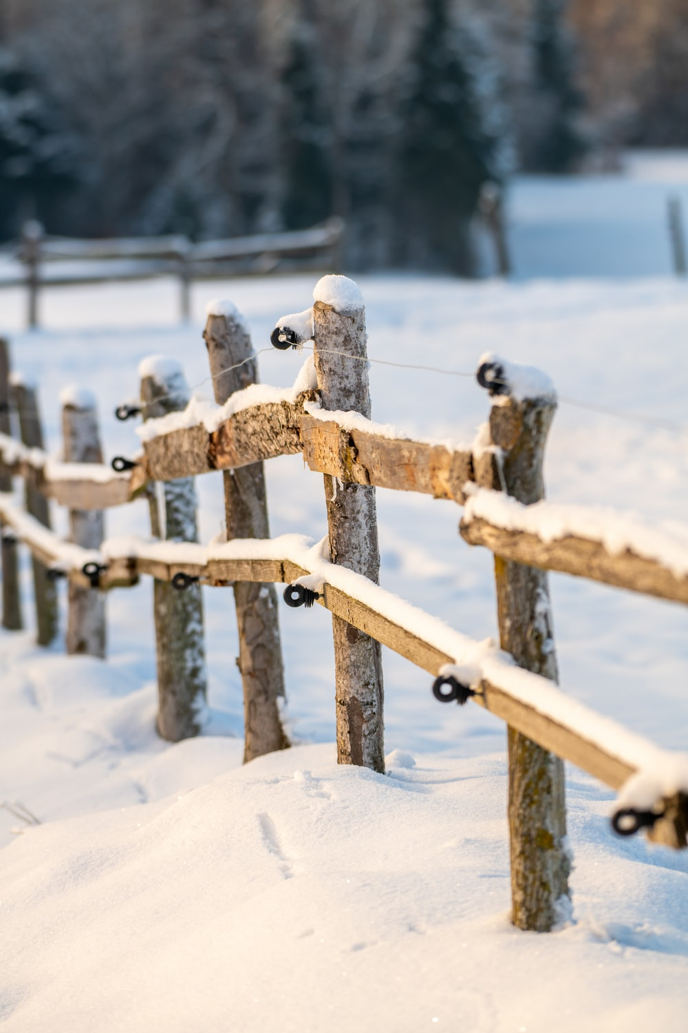 brown wooden fence covered with snow during daytime