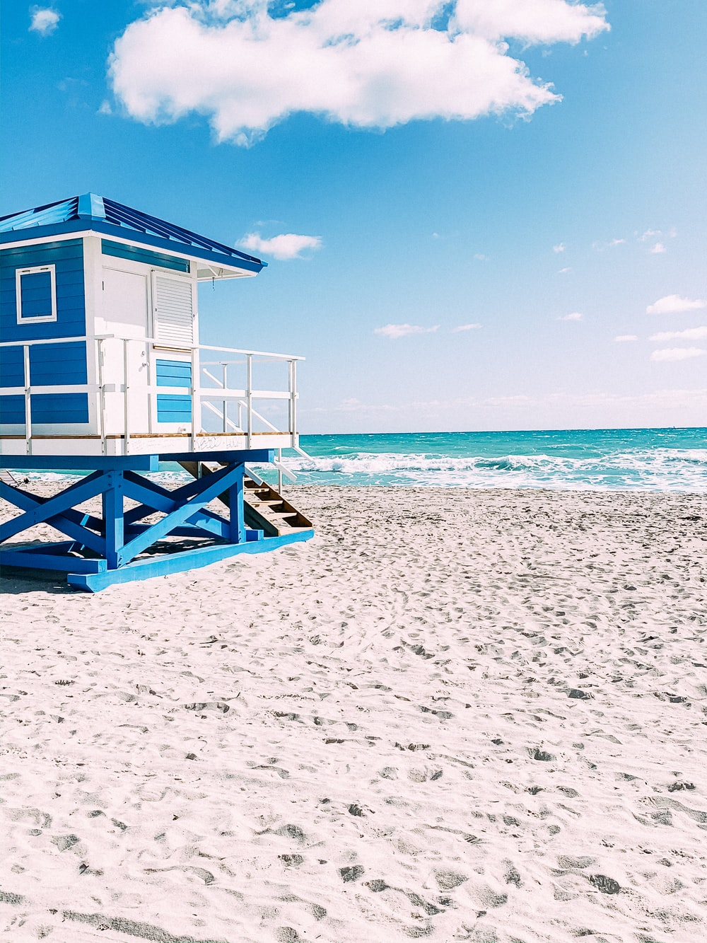 white wooden lifeguard house on beach during daytime