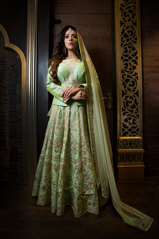 woman in green floral dress standing beside brown wooden door