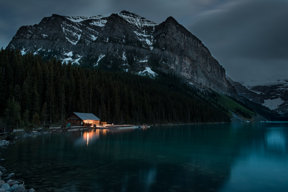 brown wooden house on lake near mountain