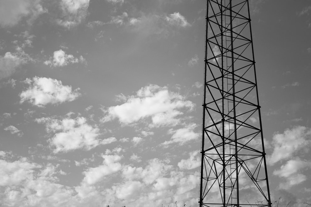 grayscale photo of electric tower under cloudy sky