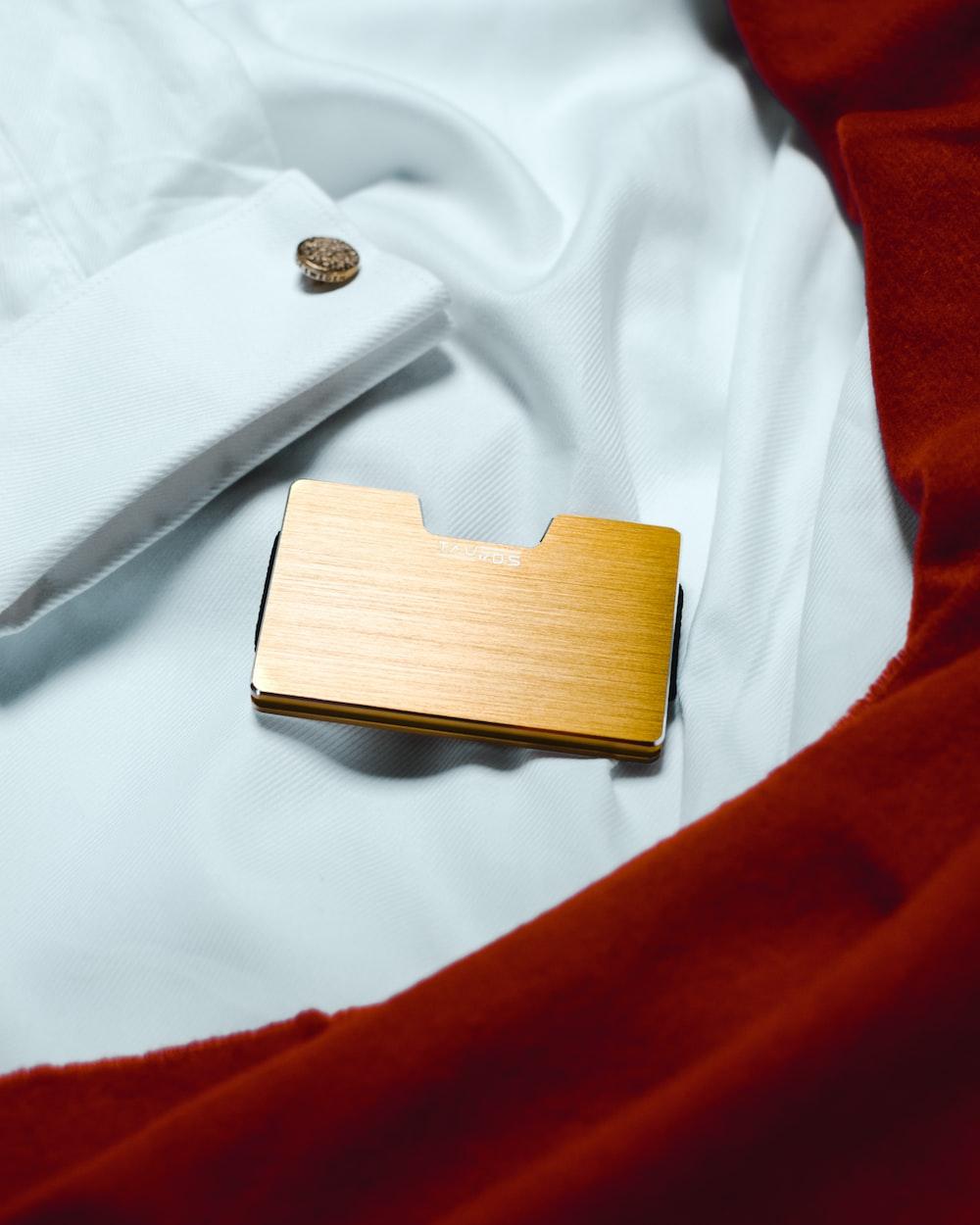 brown wooden box on white textile