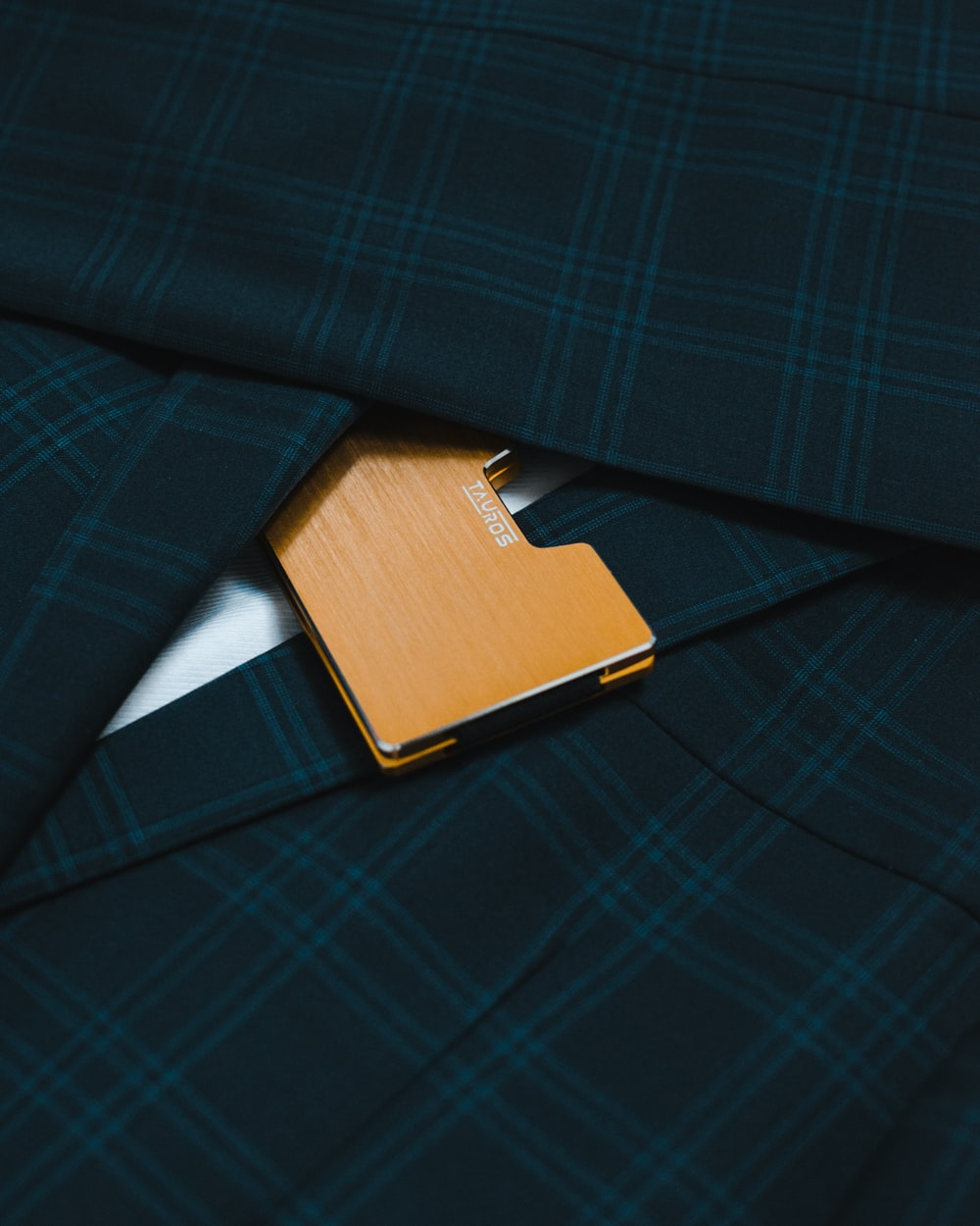 brown leather flip cover on blue and black plaid textile