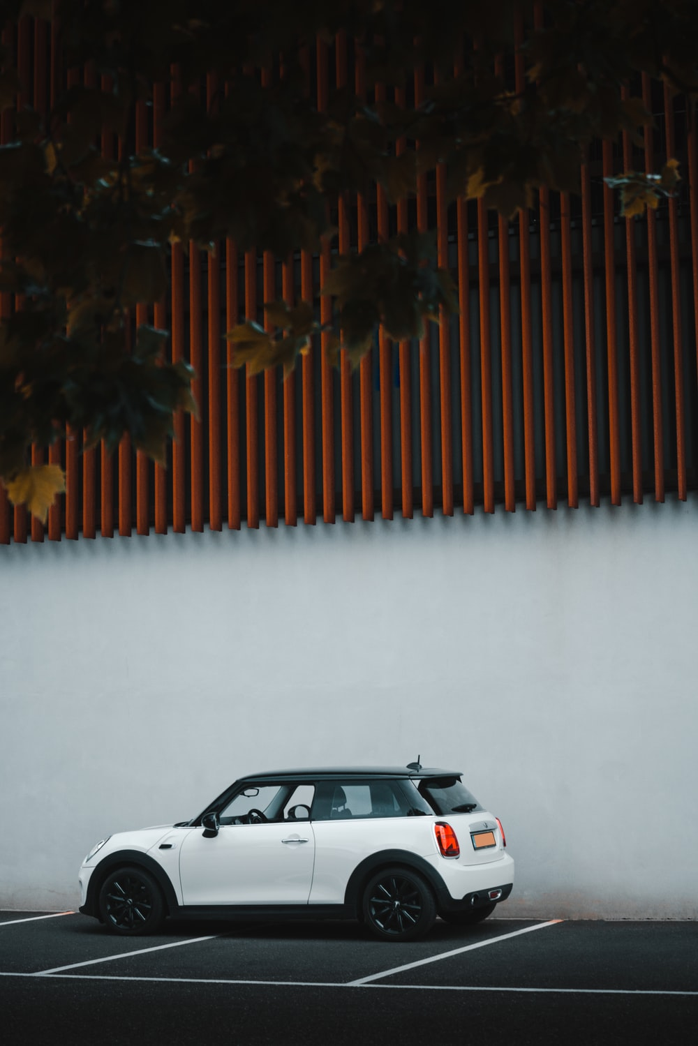 white car parked beside brown wall