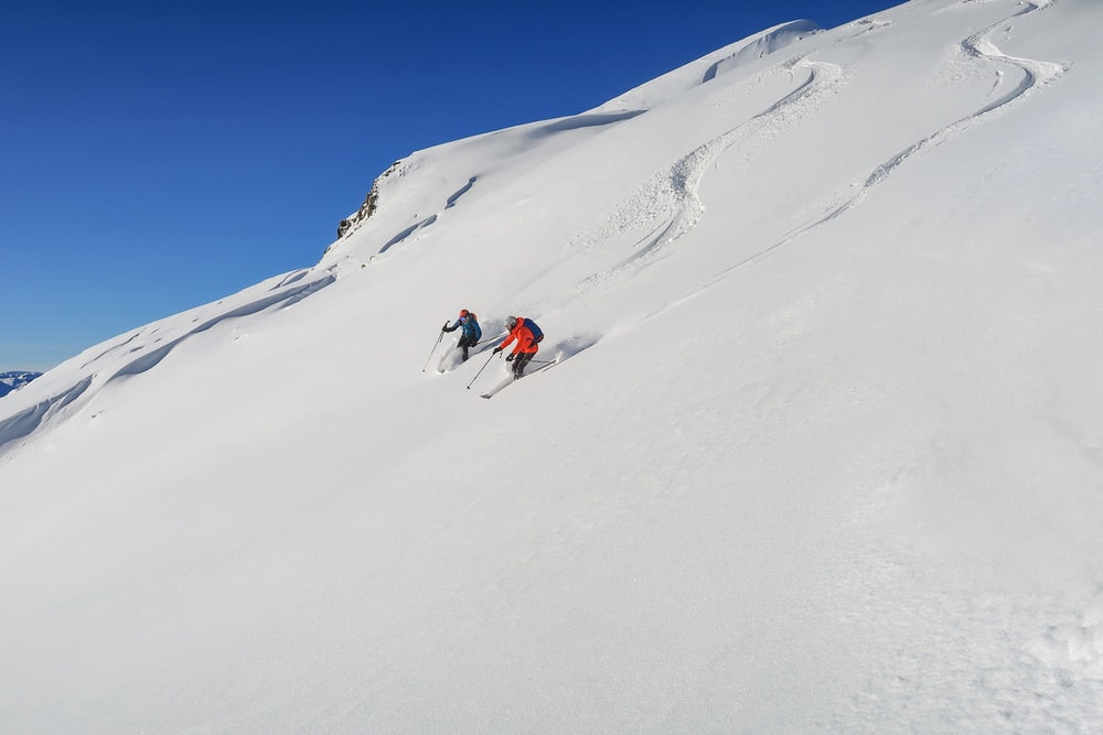 person in red jacket and blue pants on snow covered mountain during daytime