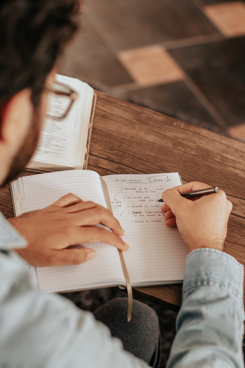 person in blue denim jeans writing on white paper