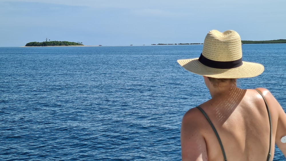 woman in brown sun hat standing near body of water during daytime