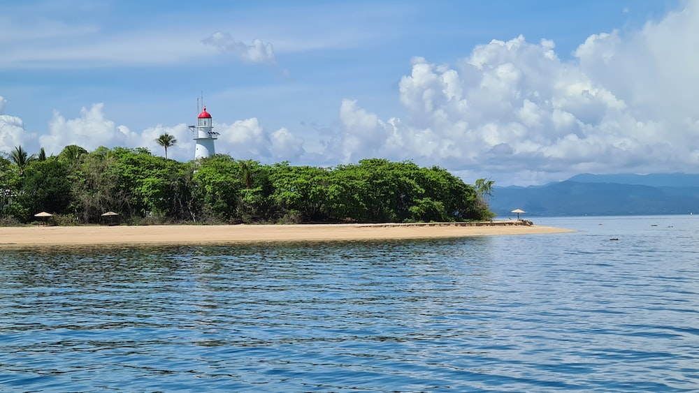 white and red lighthouse near green trees and body of water under blue and white cloudy