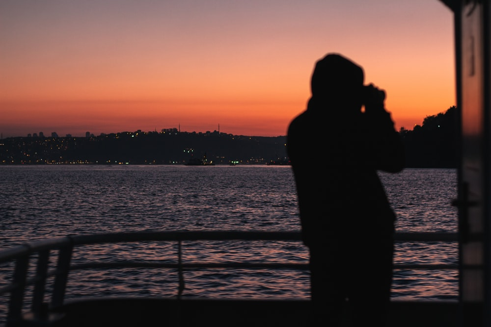 silhouette of man standing near body of water during sunset