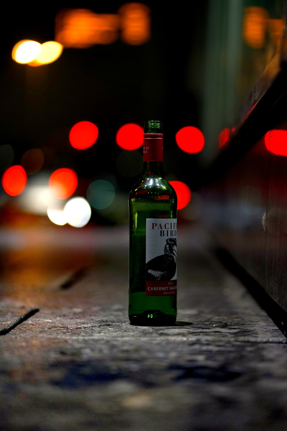 green glass bottle on brown wooden table