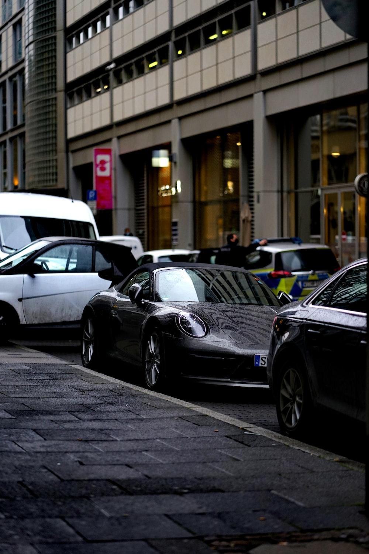 black mercedes benz c class parked on sidewalk during daytime