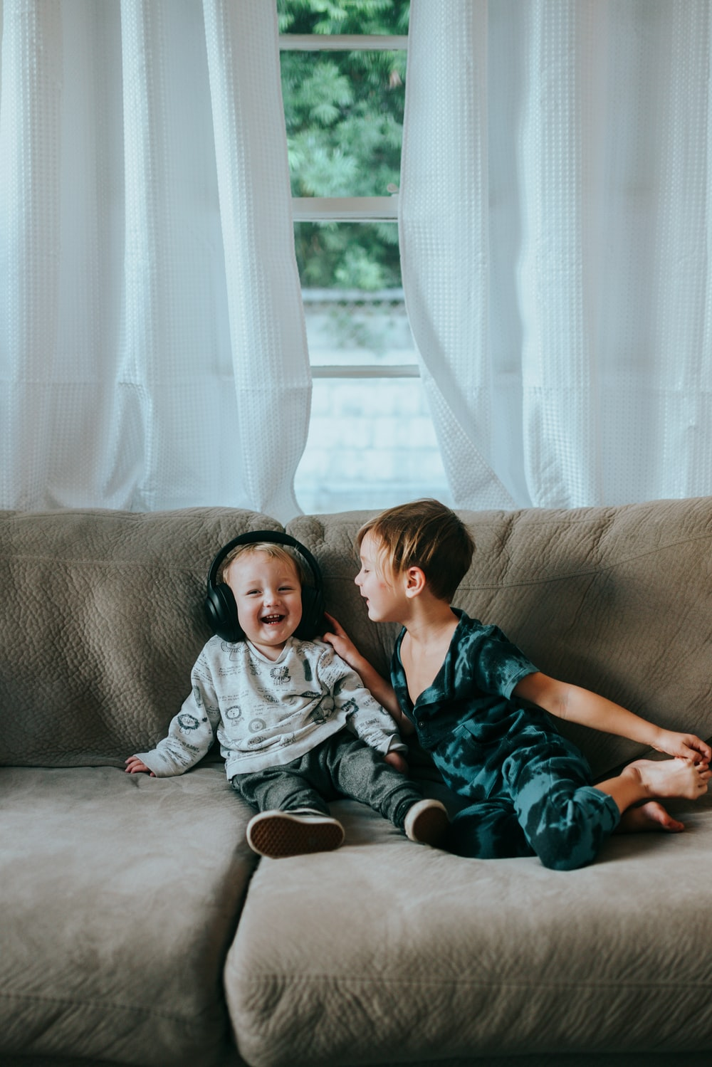2 boys and girl sitting on brown couch