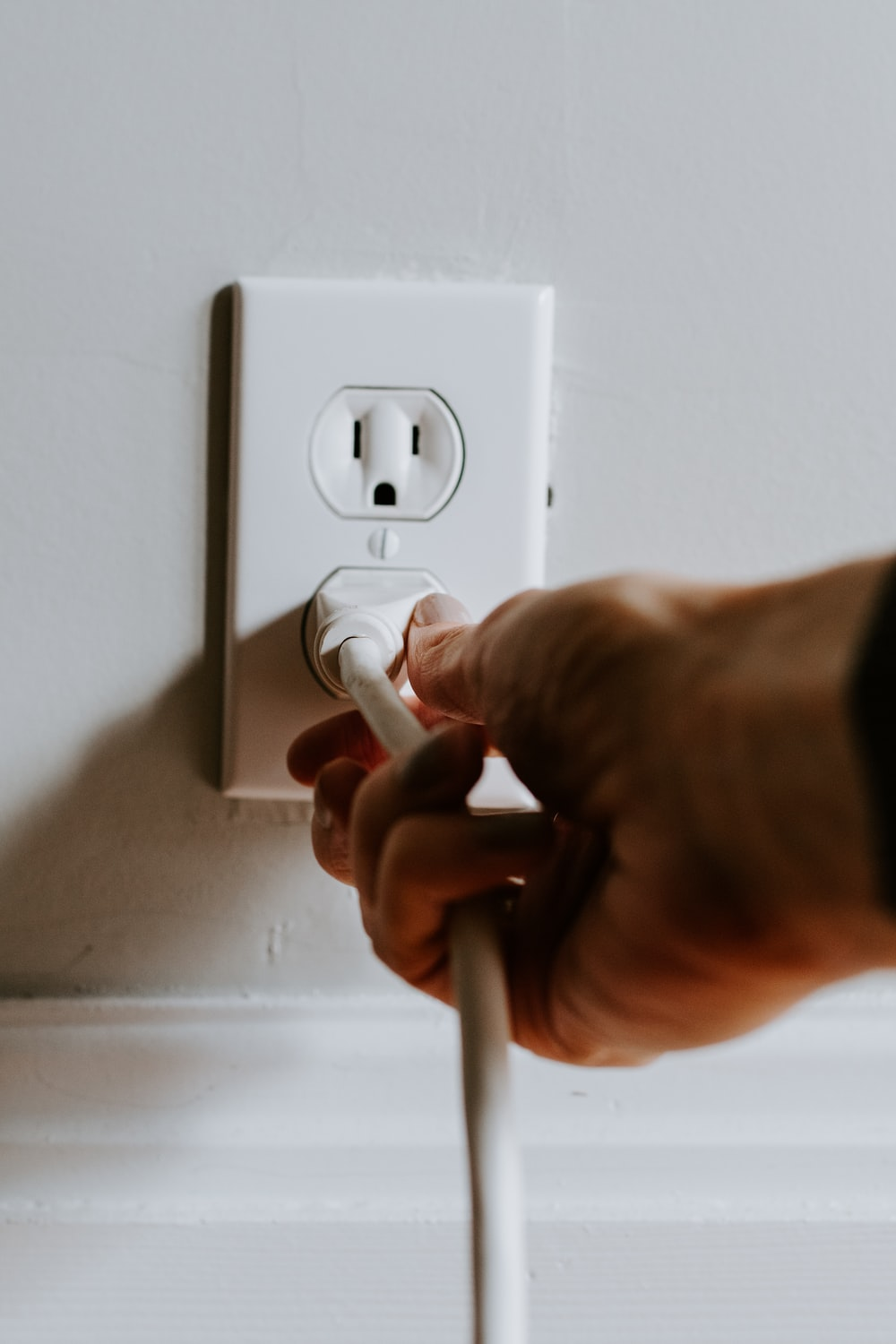 person holding white electric plug