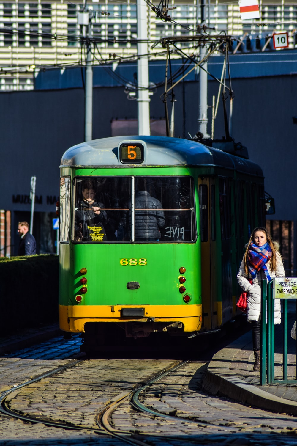 woman in white jacket standing beside yellow and white tram during daytime
