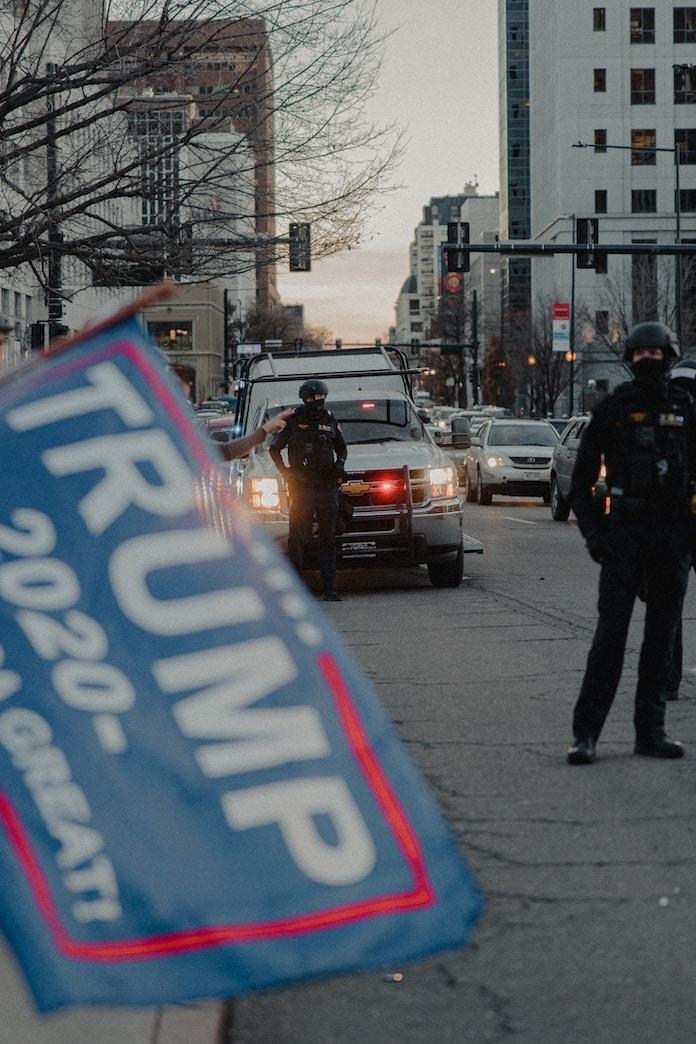 man in black jacket and black pants standing on sidewalk during daytime