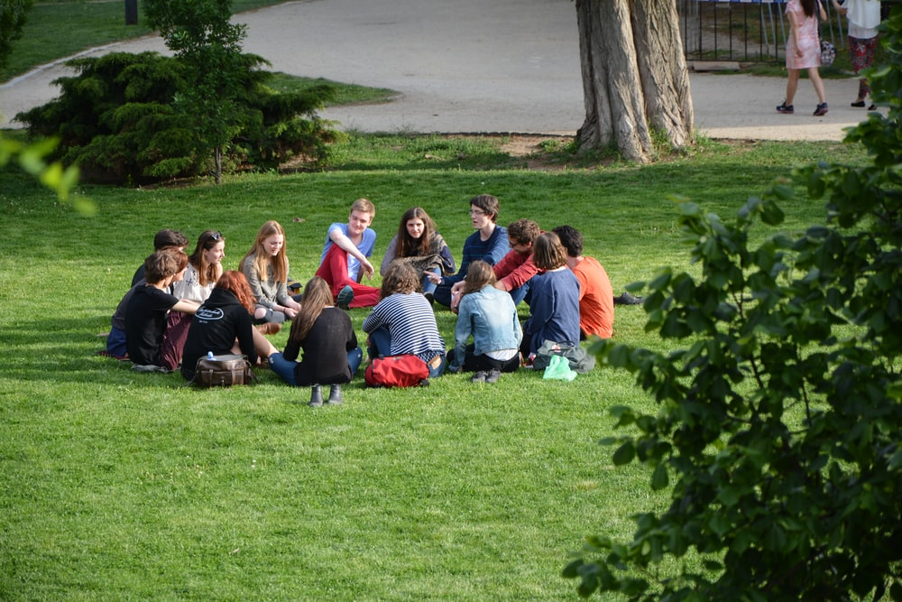 group of people sitting on green grass field during daytime