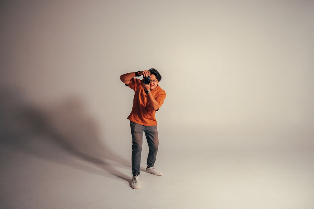 man in orange crew neck t-shirt and blue denim jeans standing and holding black camera