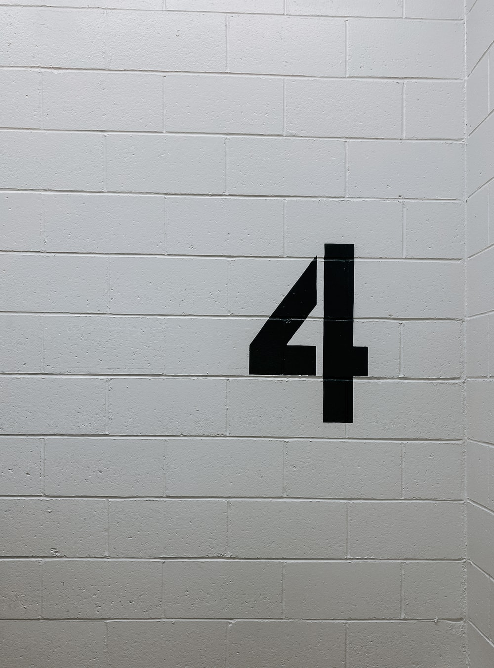 black arrow sign on white brick wall