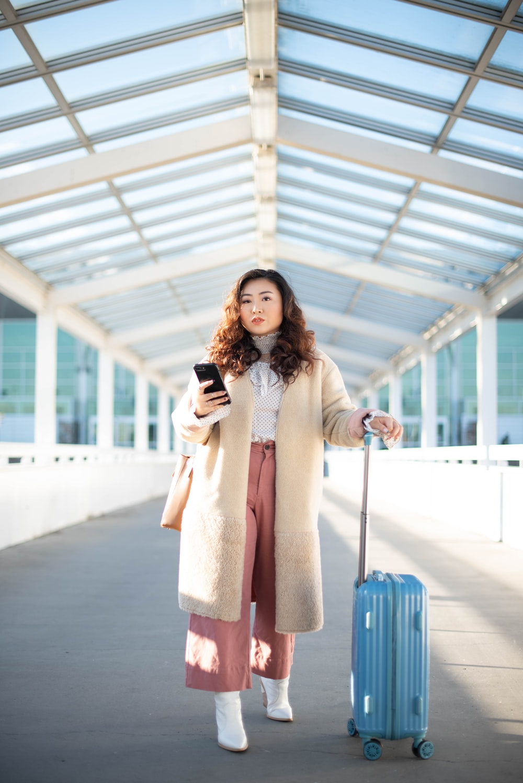 woman in beige long sleeve dress holding blue handbag