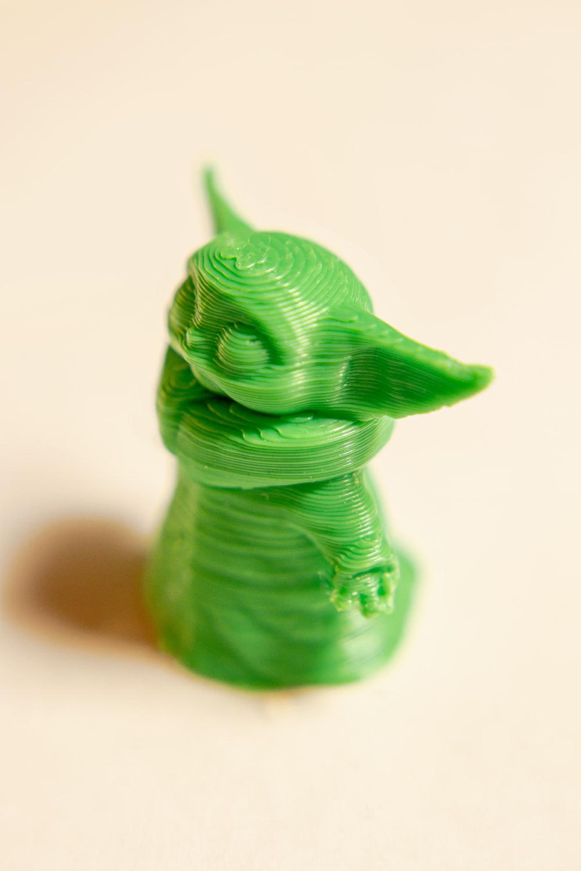 green dragon figurine on white surface
