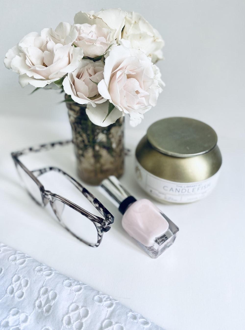 white flowers beside black framed eyeglasses and black framed eyeglasses