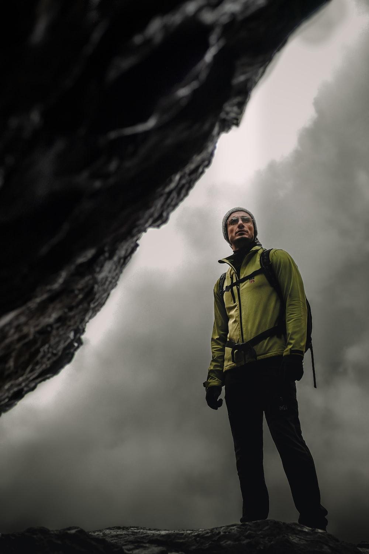 man in green jacket standing near rock formation